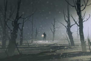 man holding lantern stands in dark forest with fog